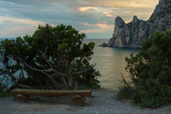 Wooden bench on background of Blue bay and mount Karaul-Oba. Royalty Free Stock Photos