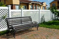 Wooden bench on the background of a white plastic fence in a country village royalty free stock photos