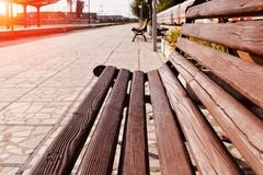 Wooden bench with backrest at the platform on the railway station at a sunset, diminishing perspective. Close up of a wooden bench with backrest at the platform royalty free stock image