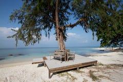 Wooden bench on the beach Stock Photos