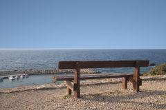 Wooden bench on the beach against the setting sun Stock Photography