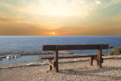 Wooden bench on the beach against the setting sun Royalty Free Stock Images