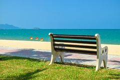 Wooden bench on beach with green lawn and flags royalty free stock photo