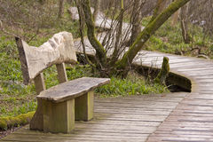 Wooden bench and boardwalk. Disappearing into the distance stock photos