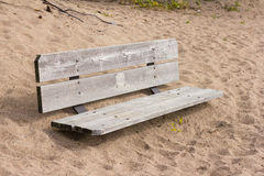 Wooden bench buried in the sand Royalty Free Stock Image