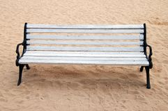 Wooden bench and butts over the sand Stock Photography