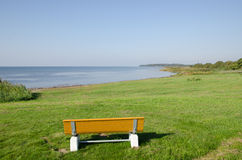 Wooden bench by a calm bay Royalty Free Stock Photos