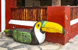 Wooden bench carved into a toucan bird shape sitting on mosiac sidewalk against bambo and stucco wall in Mexico. A Wooden bench carved into a toucan bird shape stock image