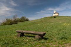 Wooden bench and chapel on hill Michelberg on a sunny day in spring. Wooden bench and chapel on hill Michelberg Lower Austria on a sunny day in spring Royalty Free Stock Photo