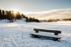 Wooden bench close to a frozen lake in Bogstadvannet Oslo. Stock Photos