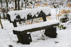 A wooden bench covered with fresh melting snow Stock Image