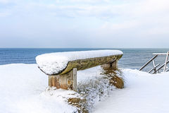 Wooden bench covered with snow on the shore of the Baltic Sea Royalty Free Stock Photo