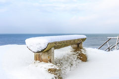 Wooden bench covered with snow on the shore of the Baltic Sea Stock Photos