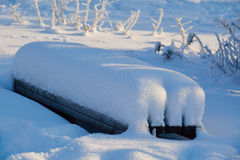 Wooden bench covered with snow, Royalty Free Stock Photography