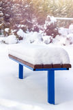 Wooden bench covered by snow in winter day. Royalty Free Stock Image