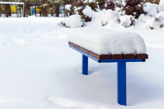 Wooden bench covered by snow in winter day. Royalty Free Stock Photos