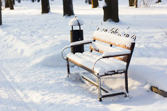 Wooden bench covered by snow in winter park. Royalty Free Stock Photography