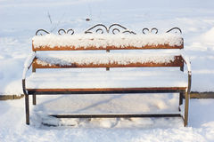 Wooden bench covered by snow in winter park. Stock Photo