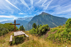 Wooden bench with cross and italian Alps in Piedmont, Italy. Royalty Free Stock Photos