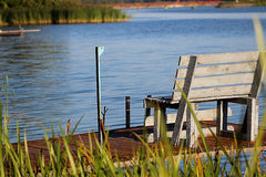 Wooden bench on the dock. By the lake at sunset Royalty Free Stock Photography
