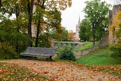 Wooden bench and fallen leaves with medieval ruins on a background in Cesis town, Latvia Stock Images