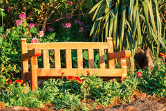 Wooden bench in flower garden Royalty Free Stock Photos
