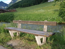 Wooden bench in forest. A wooden bench on the meadow by the river of the forest Royalty Free Stock Image