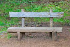 Wooden bench in the forest among dry coniferous needles and cones and grass royalty free stock photography