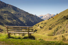Wooden bench in front of amazing view on valley and mountains P Royalty Free Stock Photos