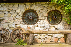 Wooden bench in front of farmhouse. Wooden bench in front of a farmhouse with stone wall and wheels wagon shaped windows Stock Photography