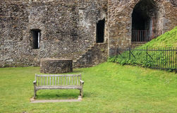 A wooden bench in front of medieval wall ruins Stock Photo