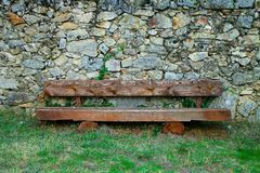Wooden Bench in Front of a Rock Wall Stock Images