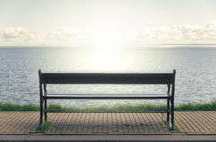 Wooden bench in front of the sea Stock Photo