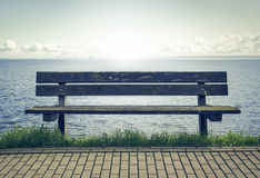 Wooden bench in front of the sea Stock Photos