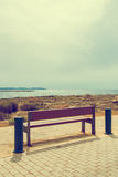 Wooden bench in front of the seashore. Stock Photo