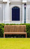 Wooden Bench in front of White Building and Street Lamp Royalty Free Stock Image