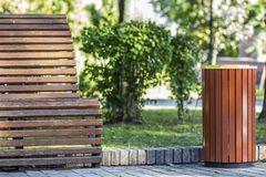 Wooden bench and a garbage bucket in park.  Stock Image