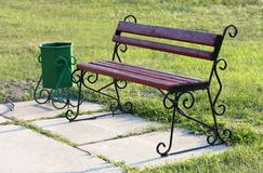 An old wooden bench stands on the lawn in the park and is painted with a brownish-red paint. A wooden bench and a garbage can in antique style stand on the green royalty free stock images