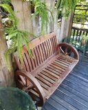 Wooden bench in garden. Backyard furniture seat chair relax family decor wood fern plants pot home green relax royalty free stock photo