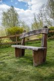 Wooden bench in the garden on meadow. Wooden bench in the garden on a meadow in spring Royalty Free Stock Images