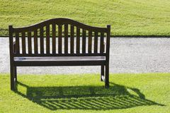 A wooden bench on a green cropped grass Royalty Free Stock Photo
