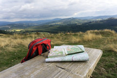 Wooden bench with hiking maps and backpack Stock Photo