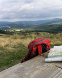 Wooden bench with hiking maps and backpack Royalty Free Stock Photo