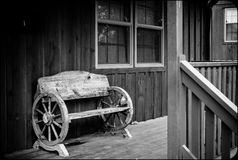 Wooden bench with horse wheels. Wooden bench made out of horse carriage stock photos