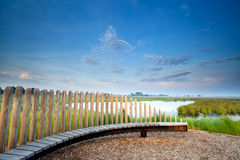 Wooden bench by lake in morning Stock Images
