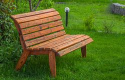 Wooden bench on a lawn with green grass Royalty Free Stock Photography