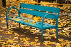 Wooden Bench With Leaves In Autumn Park. Autumn. Obsolete Wooden Bench Painted In Blue Color With Fallen Yellow Leaves In Autumn Park Outdoor royalty free stock photos