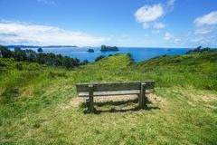Wooden bench at cathedral cove,coromandel peninsula, new zealand. Wooden bench in lush green grass at cathedral cove,coromandel peninsula, new zealand Stock Images