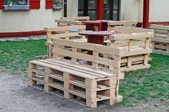 Wooden bench made of pallets for sitting with tables made from coil of electric cable Stock Image