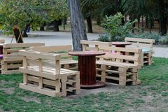 Wooden bench made of pallets for sitting with tables made from coil of electric cable Stock Photo